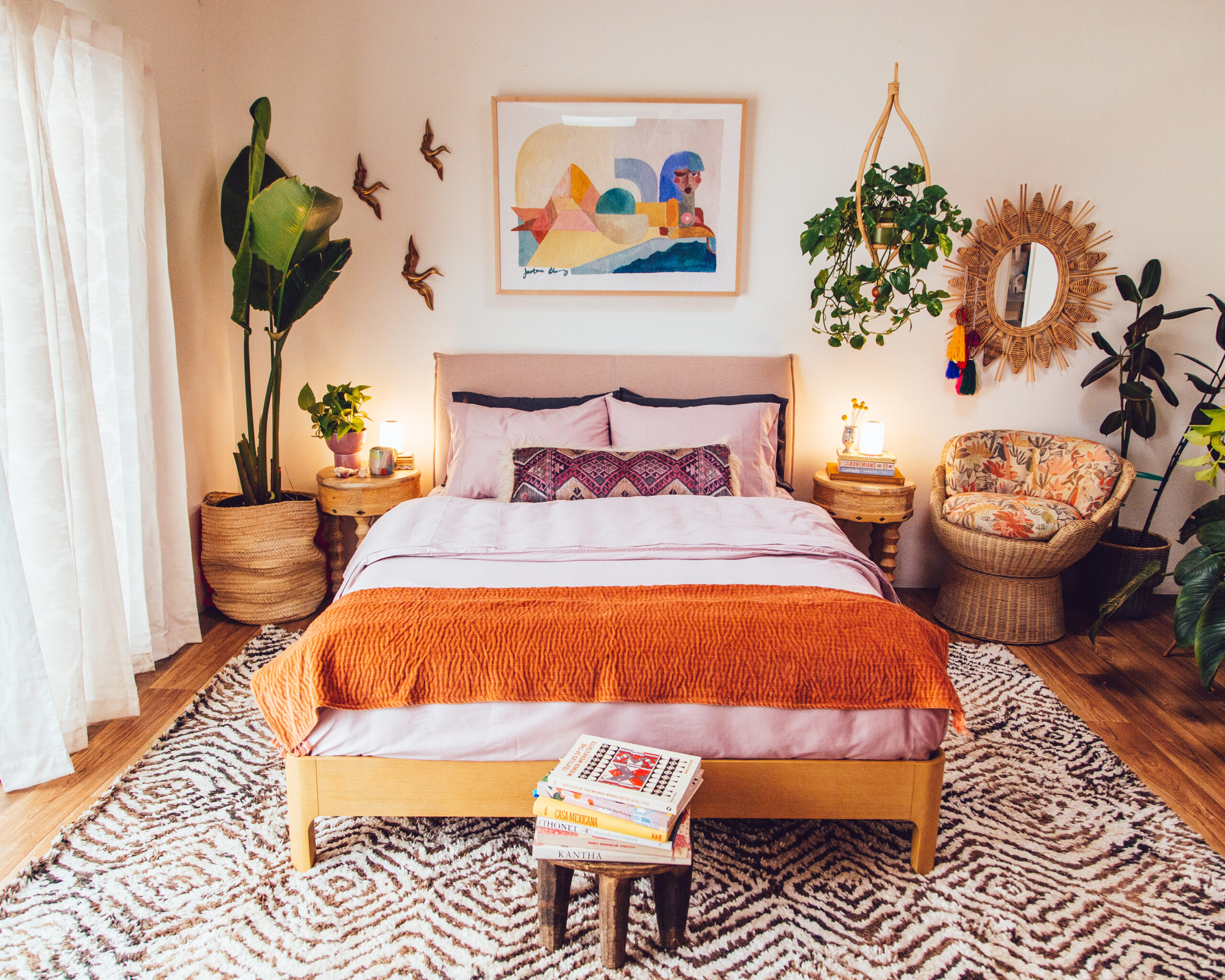 colorful bedroom with plants, pink sheets, and a printed rug