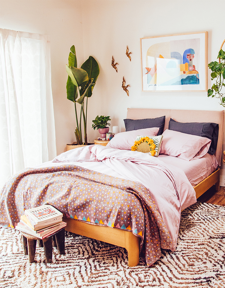 bedroom with pink sheets, plants, and wall decor