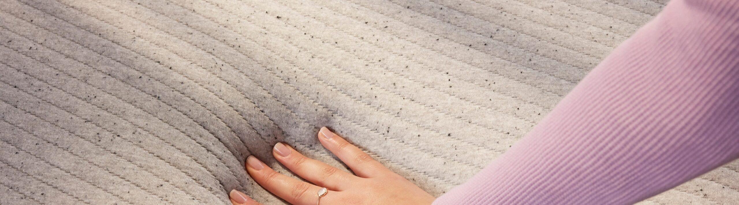 Woman's hand pushing down the memory foam mattress
