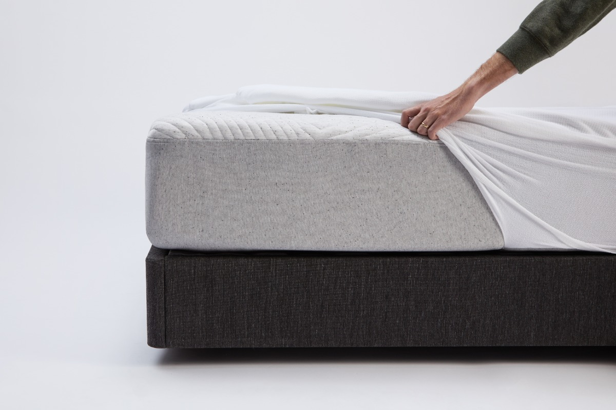 Man putting a mattress protector on a bed