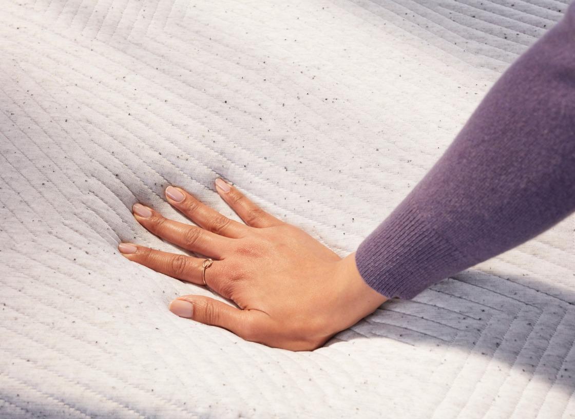 womans hand sinking into soft mattress