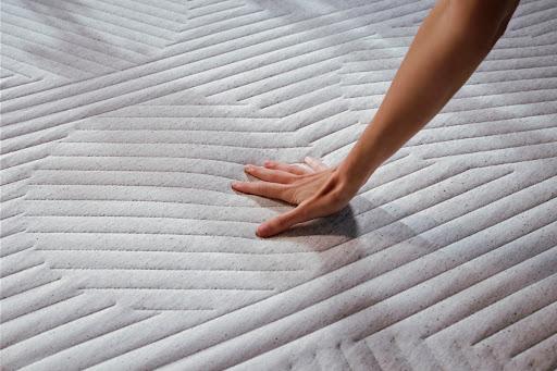 Woman's hand pushing the mattress