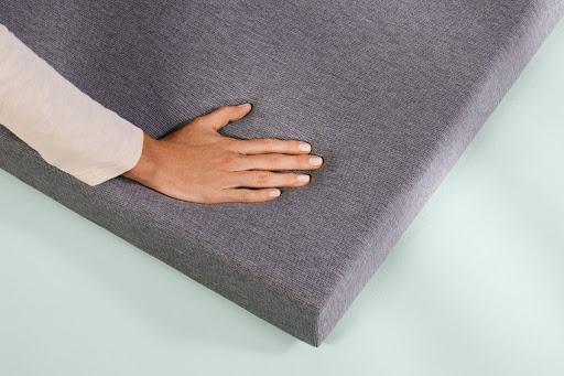 woman holding hand on mattress topper