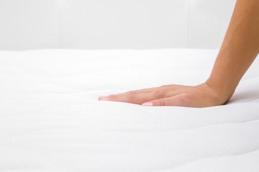 woman's hand on mattress topper