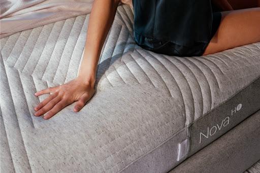 Young woman sitting on Nova hybrid mattress